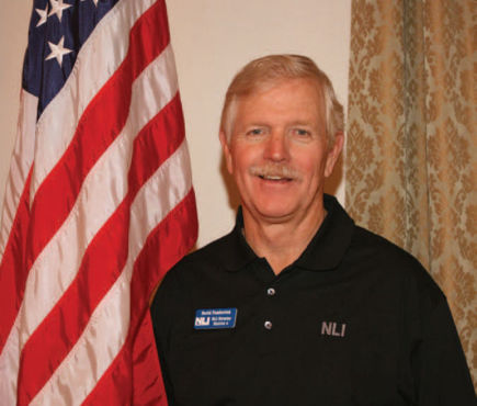 David Pemberton standing next to American flag