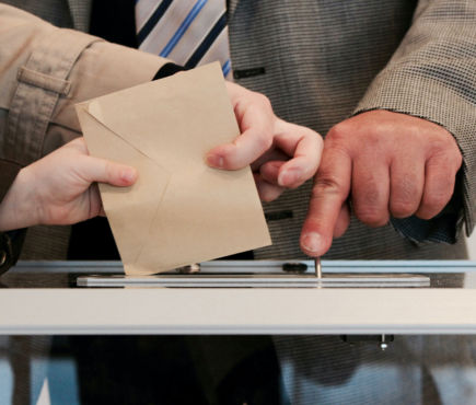 hands putting ballot in box