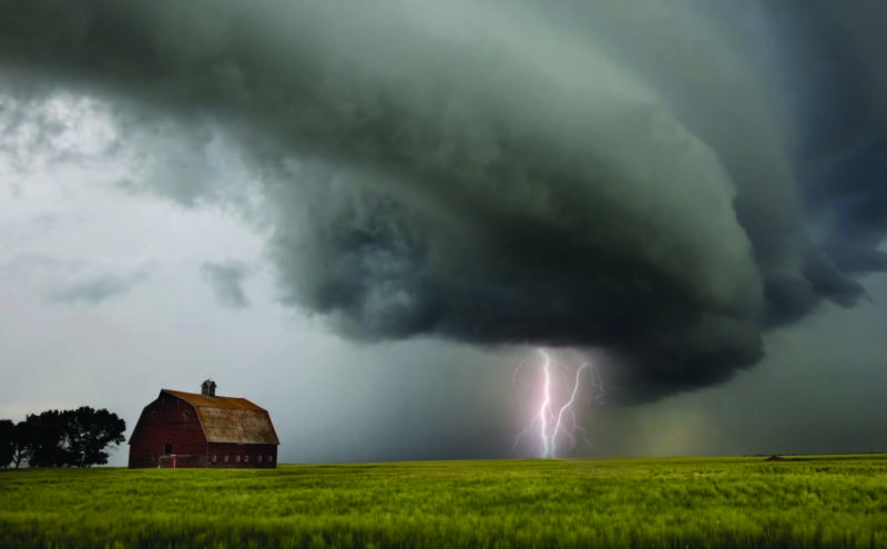 A lightning bolt is seen connecting the ground to a dark cloud overhead. A barn is seen in the distance to the left.