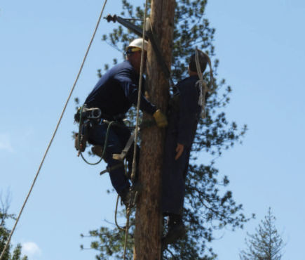 Two lineworkers on a power pole.