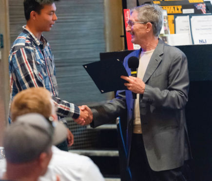 NLI Board President Steve Elgar presents Victor Zhong with his scholarship certificate.