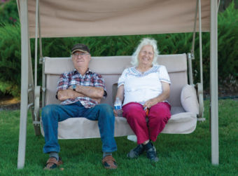 Elderly couple sitting on swing