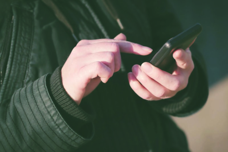 A person hold a mobile phone in one hand and taps the screen with their other hand