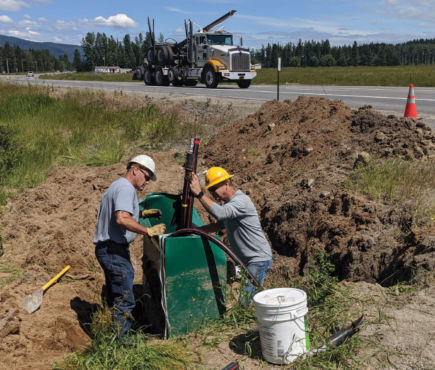 Two linemen repairing a junction box in the dirt on the side of a road.
