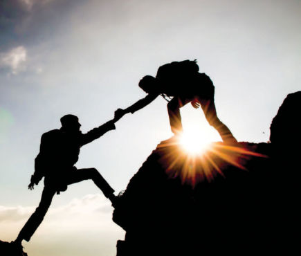 two people helping each other climb a mountain