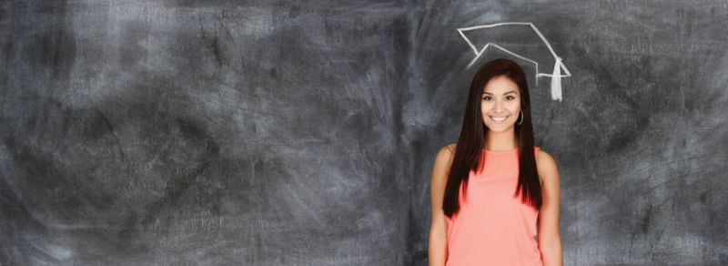 young woman stands smiling in front of chalk board
