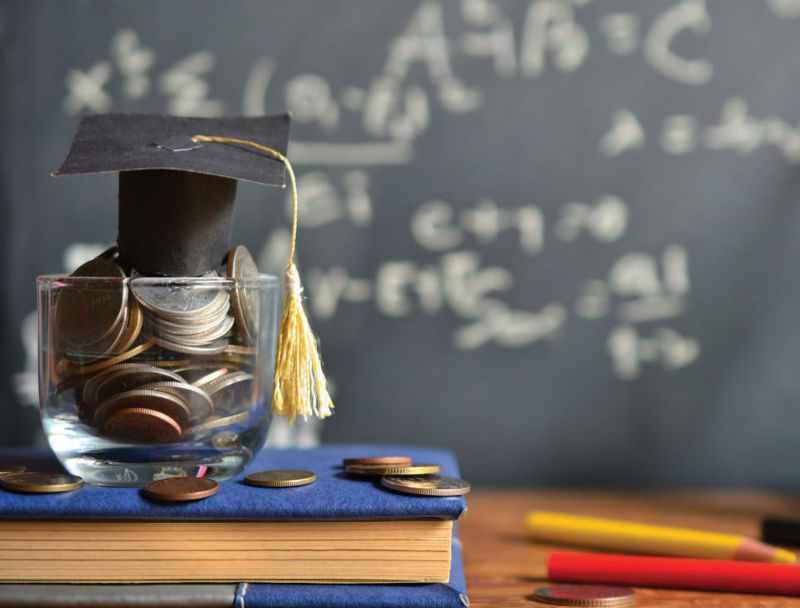 jar with coins with graduation cap on school desk