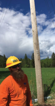 Lineman standing next to power pole.