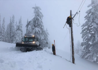 lineman on power pole working in the snow