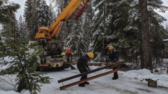 NLI linemen prepare to install a power pole in snowy woods. Photo by Kristin Mettke