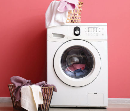 Washing machine with laundry basket nearby filled with towels