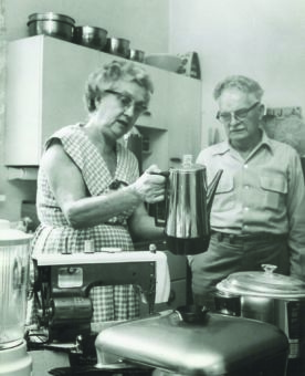Black and white photo of an older woman and man looking at appliances in a kitchen.